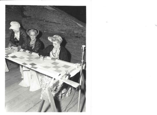 History Mystery Photo #7  The Heyworth Public Library holds in it's archive this picture from the Heyworth Centennial Celebration play. These women are seated quilting as part of an act in the play.  We are wanting to know the identities of these ladies. If anyone can give any information as to who they are, we would be very interested in learning more.