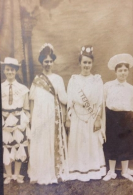 History Mystery Photo #2 This second photo goes with the group photo #1. The four ladies can be found in the group picture #1. One girl is wearing a Columbia hat, with the girl next to her (on the right) wearing a banner that reads: Battershell. The other two ladies have unique costumes as well. There are four names on the back of the picture: Alma Washburn Downs, Bess Groves Streepe (telephone operations), Pearl Battershell Cusey, and Della Van Valey Van Ardshant (spelling may not be correctly deciphered). This picture will also be on display at the Heyworth Library, and any information to help the Heyworth History Club correctly record this historical moment in Heyworth History would be welcome.