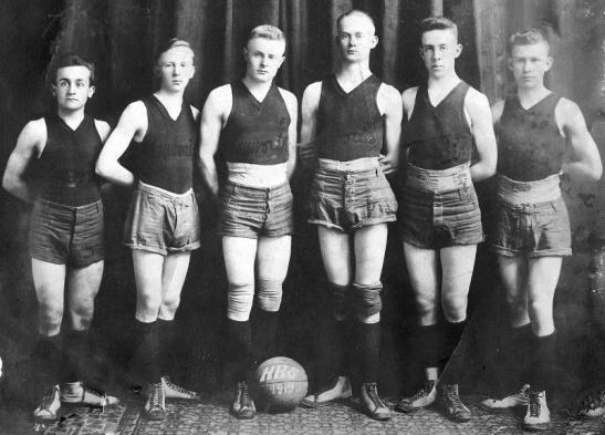 History Mystery Photo #6  The Heyworth Public Library holds in it's archive this picture a Heyworth High School basketball team from 1919.  We thought this would be fun to look at after the amazing game last week of our current boys basketball team.  We don't think the shoes look all that comfortable, nor the knee-pads all that helpful compared to today's standards.  If anyone can give any information about this team or if you hold a yearbook from this year, we would be very interested in learning more.