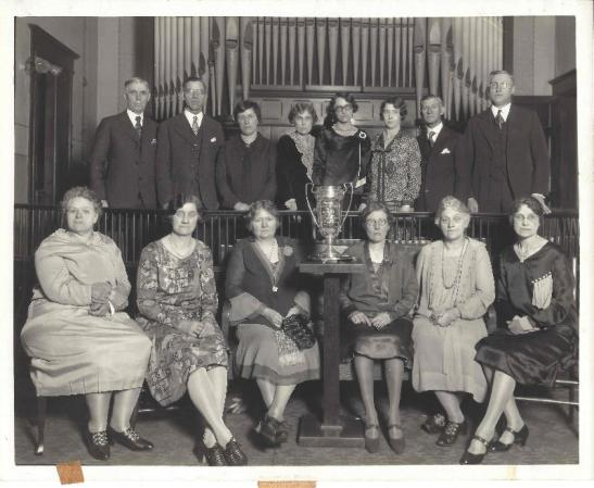 History Mystery Photo #8  In 1928 the General Federated Women entered and won The Cleanest Town in IL (based on size/population) for the Village of Heyworth. The Village of Heyworth also won this award in 1929 and 1930 through the efforts of the GFWC. If you know any more details of this event, or the people sitting for the picture we would love to know more information.  All three trophies are on display in the front case of the library until the end of April, along with a 1914 plat map of Randolph Township.  The trophies are on loan from the Village of Heyworth.