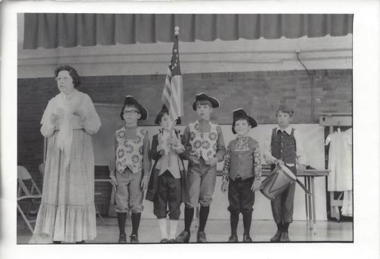 History Mystery Photo #11.  During Bi-centennial celebrations this picture was taken of Maurita Cusey with these students.  We are wanting to know who these children are in the picture.  If you have any information to share as to who is in this picture, where and what they were doing, please call the library and give us more information to complete the history of this picture at 473-2313.